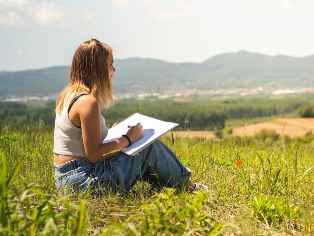 Femmina caucasica seduta e disegno nella natura