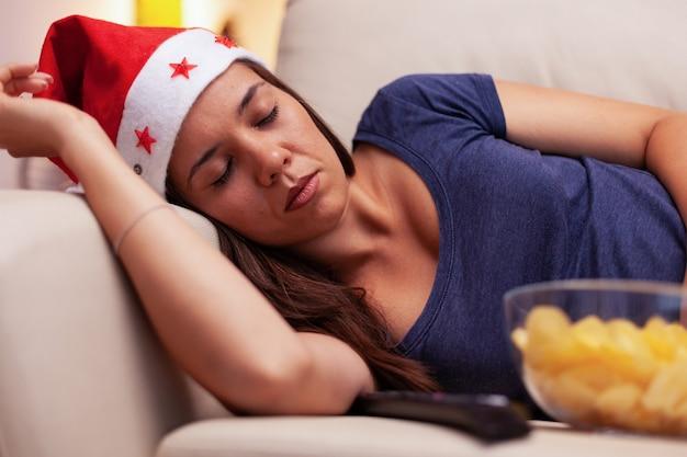 Femmina caucasica che dorme sul divano dopo aver visto un film di intrattenimento natalizio