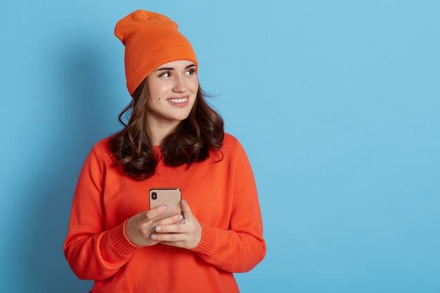 Femmina caucasica che indossa abbigliamento casual in posa con smart phone in mano e distoglie lo sguardo con un sorriso piacevole e l'espressione facciale sognante, isolato sopra la parete blu. copia spazio.