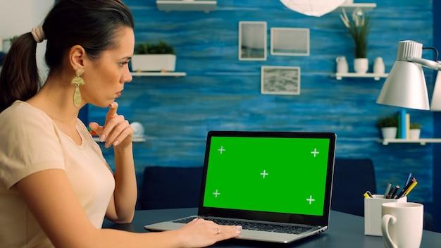 Femmina caucasica che lavora al progetto di comunicazione aziendale su computer portatile con display chroma key schermo verde green