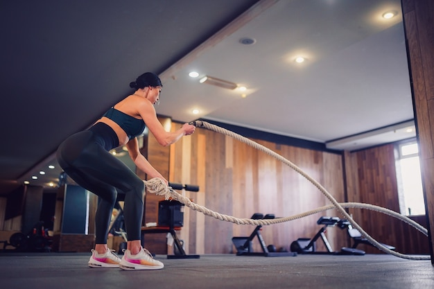 La donna in forma caucasica si è vestita in abbigliamento sportivo in posa con la corda di battaglia