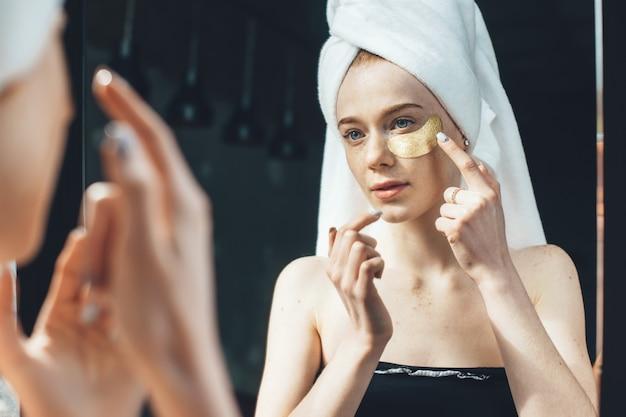 La donna lentigginosa caucasica sta applicando le bende dell'occhio dell'idrogel dorato sotto gli occhi dopo aver fatto la doccia e si copre la testa con un asciugamano