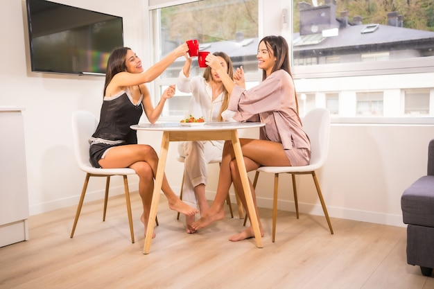 Amici caucasici in vacanza in un hotel facendo colazione, vestiti in pigiama e bevendo caffè