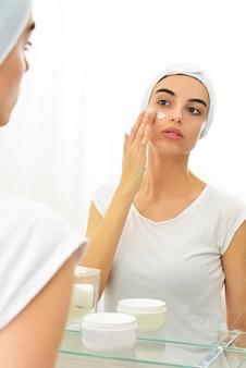 Ragazza caucasica che applica la maschera facciale davanti allo specchio