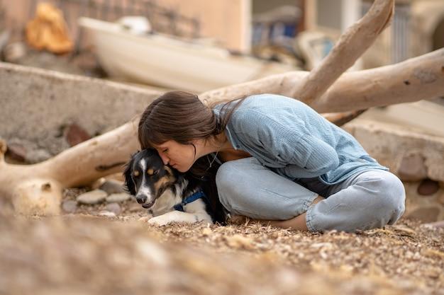 Ragazza caucasica sulla spiaggia con il suo cane che le accarezza il viso