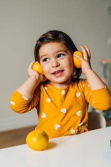 Ragazza caucasica divertendosi con i mandarini. dieta sana del bambino. potenziamento immunitario con vitamina c. foto di alta qualità
