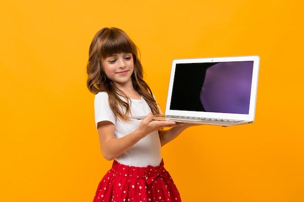 La ragazza caucasica tiene lo schermo del taccuino con il modello in avanti sull'arancia