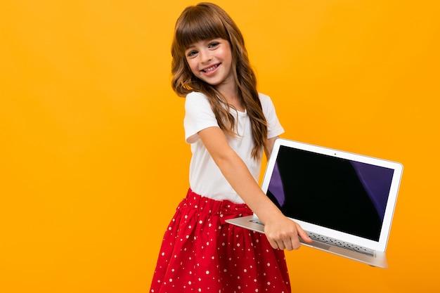La ragazza caucasica tiene lo schermo del taccuino con il modello in avanti su giallo