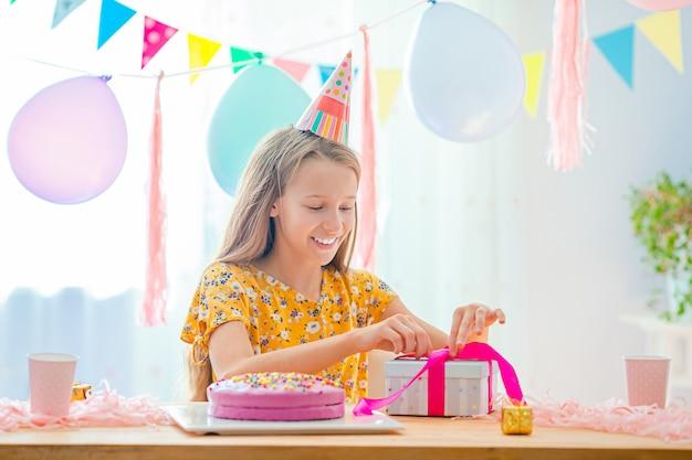 La ragazza caucasica sta sognando sorridendo e guardando la torta arcobaleno di compleanno. sfondo colorato festivo con palloncini. festa di compleanno e auguri concetto.