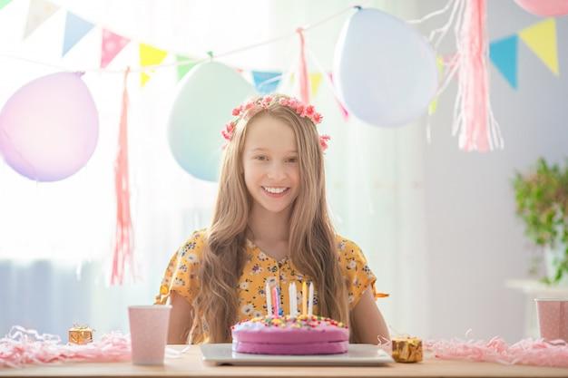 La ragazza caucasica sta sognando sorridendo e guardando la torta arcobaleno di compleanno. sfondo colorato festivo con palloncini. festa di compleanno e auguri concetto. Foto Premium