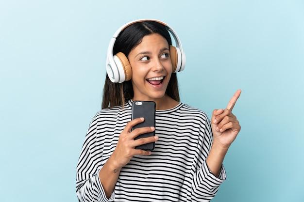 Ragazza caucasica isolata sulla musica d'ascolto blu con un cellulare e cantando