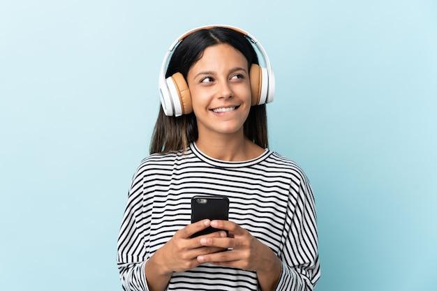 Ragazza caucasica isolata sulla musica d'ascolto blu con un cellulare e un pensiero