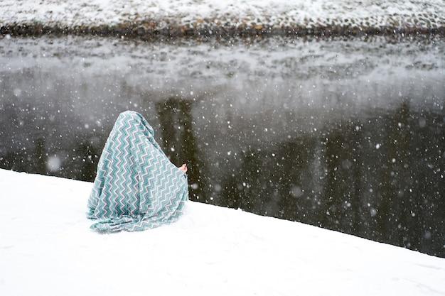 Jogi ragazza caucasica coperto di coperta seduto in asana e pratica joga durante la nevicata vicino al fiume