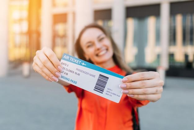 Ragazza caucasica gioiosa in possesso di un biglietto aereo per l'aereo e viaggia nelle sue mani.