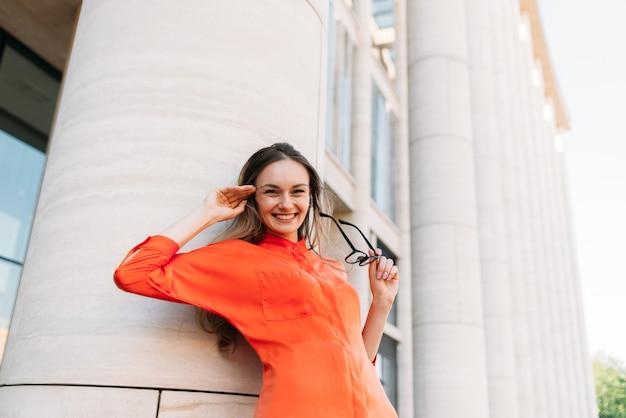 La ragazza caucasica gioiosa tiene gli occhiali in mano e si appoggia su un edificio moderno.