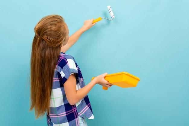 La ragazza caucasica dipinge una parete con un rullo e una vernice isolati sul blu