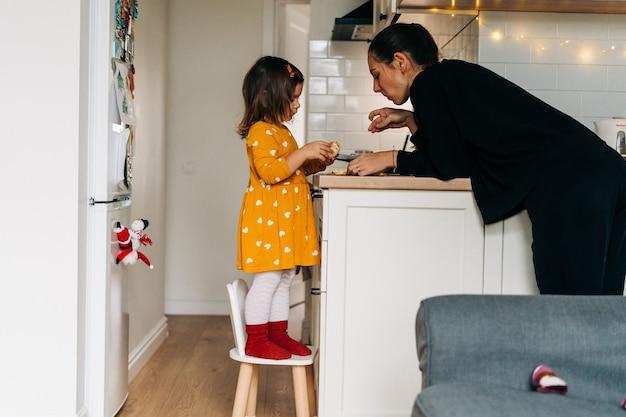 Ragazza caucasica sbucciare i mandarini sul bancone della cucina. dieta sana del bambino. potenziamento immunitario con vitamina c. foto di alta qualità