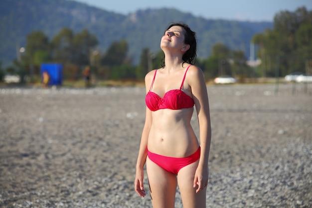 Ragazza caucasica in costume da bagno rosa, in piedi sulla spiaggia di ciottoli in turchia, faccia al sole e gli occhi chiusi, località turistica.