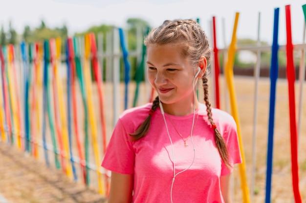 La ragazza caucasica in una maglietta rosa e cuffie bianche ascolta musica. la studentessa sorride, esponendo il viso ai raggi del sole.