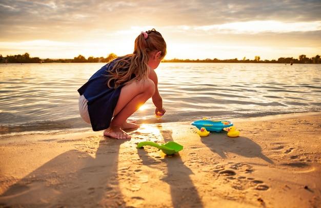Ragazza caucasica che gioca con i giocattoli di gomma dell'anatra sulla spiaggia.