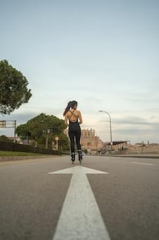 Ragazza caucasica su pattini a rotelle in piedi sulla strada sul lungomare di palma de mallorca al tramonto