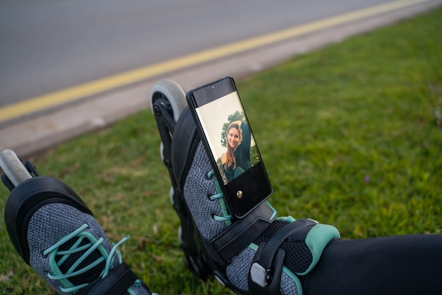 Ragazza caucasica seduta sull'erba con i pattini guardando uno smartphone e sorridendo al tramonto