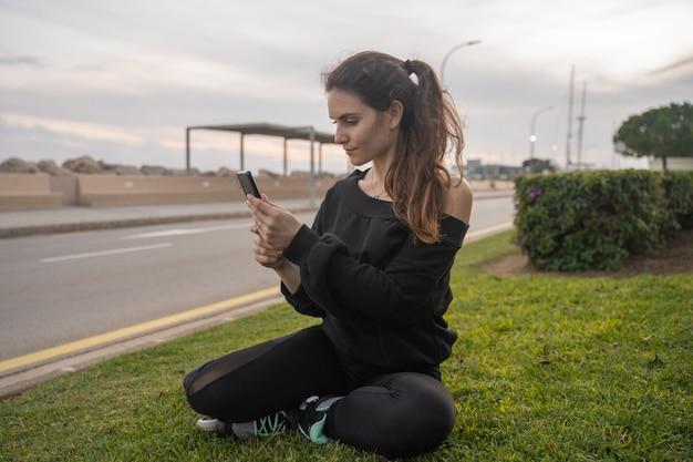 Ragazza caucasica seduta sull'erba con i pattini guardando uno smartphone al tramonto