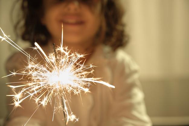 Ragazza caucasica sorridente fuori fuoco sfondo con sparkler in mano in primo piano