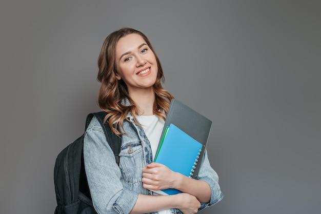 Studentessa caucasica in giacca di jeans con cartella, libri, taccuino, blocco note in mani sorridente isolato sul muro grigio scuro dello studio, copia dello spazio