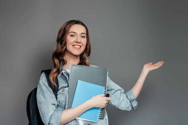 Studente di ragazza caucasica che tiene cartelle, libri, quaderni, taccuini in mani sorridendo e indicando con il dito allo spazio vuoto della copia per testo isolato sul muro grigio