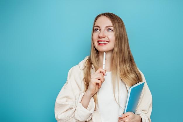 La studentessa caucasica pensa, sogna, immagina e tiene un blocco note, un taccuino, un libro isolato su una parete blu in studio. test, esami, concetto di educazione. copia spazio