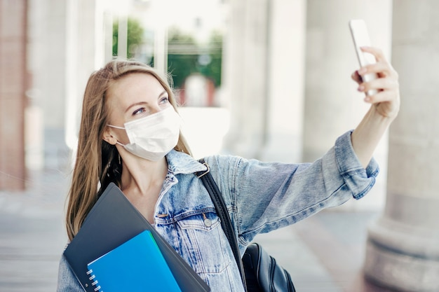 Studentessa caucasica che indossa una mascherina medica tiene in mano cartelle e quaderni e chiama in videoconferenza durante la quarantena del coronavirus