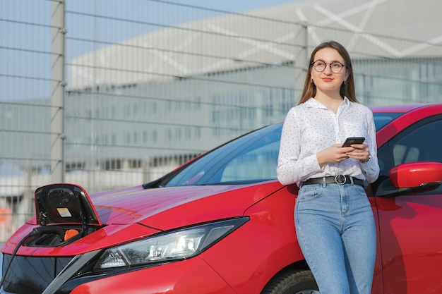 La ragazza caucasica che per mezzo dello smart phone e l'attesa dell'alimentazione elettrica si collega ai veicoli elettrici per caricare la batteria in automobile. auto ecologica collegata e ricarica batterie.