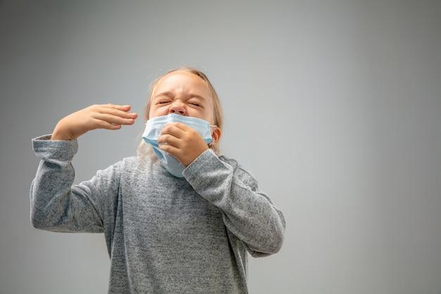Ragazza caucasica che indossa il fermaglio per la protezione delle vie respiratorie contro l'inquinamento atmosferico