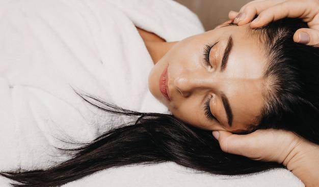 La ragazza caucasica con i capelli neri e gli occhi chiusi sta facendo un attento massaggio alla testa durante una procedura anti stress