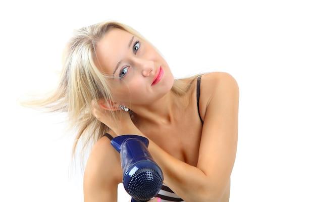 Ragazza caucasica con capelli biondi, 34 anni, usa un asciugacapelli in plastica blu, creando un'acconciatura.