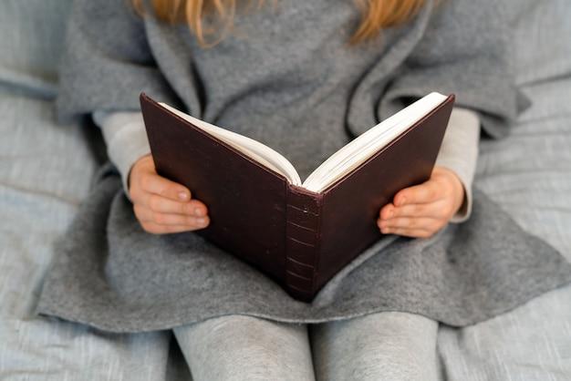 Ragazza caucasica con capelli biondi che legge un libro, scuola domestica in quarantena.