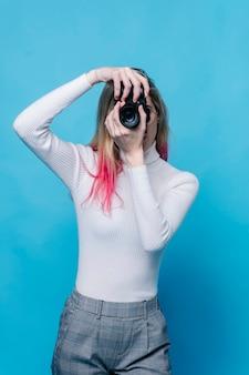 La ragazza caucasica con capelli biondi e rosa scatta una foto con una macchina fotografica isolata sull'azzurro