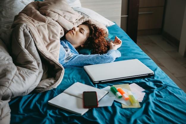 Ragazza caucasica con i capelli ricci addormentarsi nel suo letto coperto con una trapunta dopo aver fatto i compiti con il suo laptop