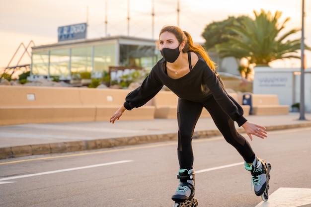 Ragazza caucasica con la maschera che pattina sui pattini a rotelle al tramonto