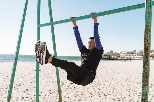 Ragazzo caucasico 20s in tuta nera che fa acrobazie sulla barra ginnica orizzontale durante l'allenamento mattutino in riva al mare