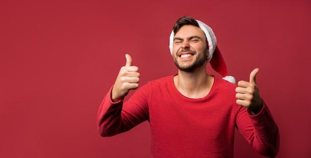 Ragazzo caucasico in maglione rosso e cappelli di babbo natale