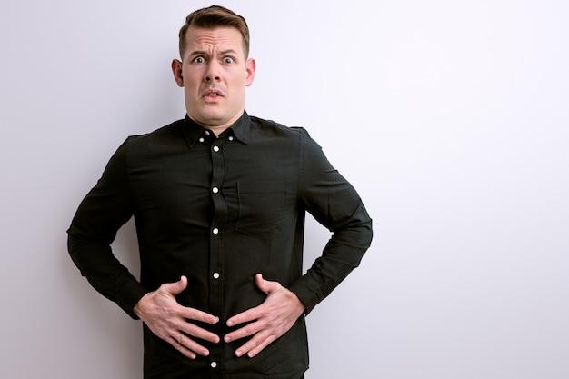 Ragazzo caucasico soffre di mal di stomaco uomo malato con mal di stomaco, gas allo stomaco, intossicazione alimentare
