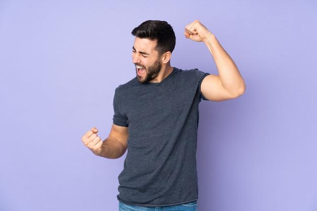 Uomo bello caucasico che celebra una vittoria sopra la parete viola isolata