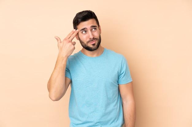 Uomo bello caucasico isolato sulla parete beige con problemi che fanno gesto di suicidio