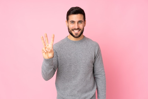 Uomo bello caucasico sopra la parete isolata felice e che conta tre con le dita
