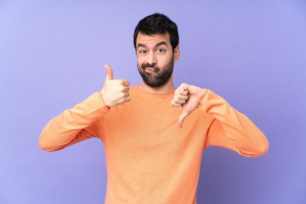 Uomo bello caucasico sopra la parete viola che fa segno buono-cattivo. indeciso tra sì o no