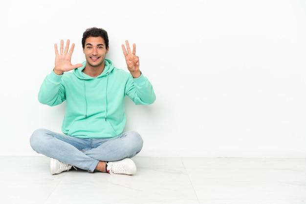 Bell'uomo caucasico seduto sul pavimento che conta otto con le dita