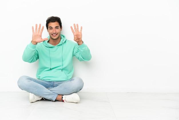 Bell'uomo caucasico seduto sul pavimento che conta nove con le dita