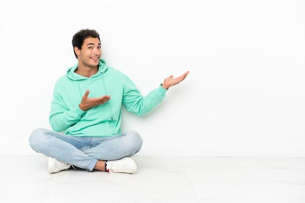 Bell'uomo caucasico seduto sul pavimento che allunga le mani di lato per invitare a venire